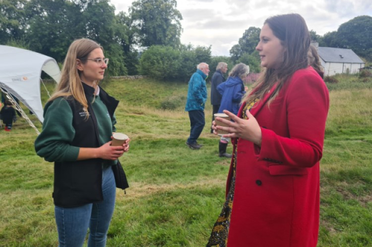 Emma stands in a red coat facing a young female Woodlands Trust volunteer. They are deep in conversation.