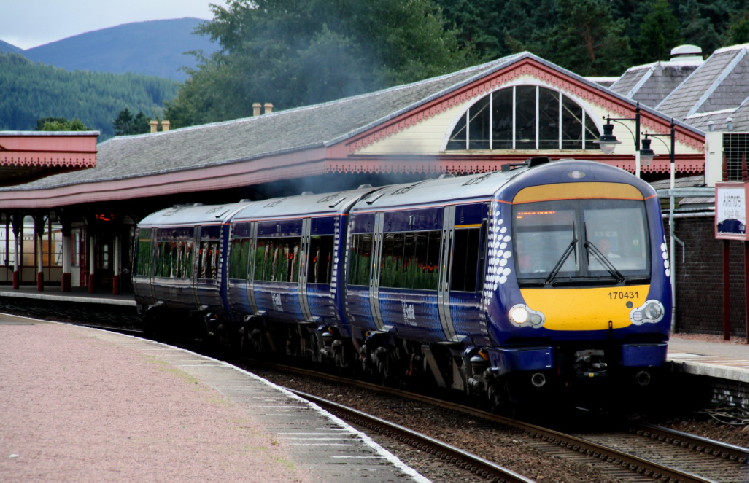 A yellow and blue ScotRail class 170 train leaves Aviemore Station