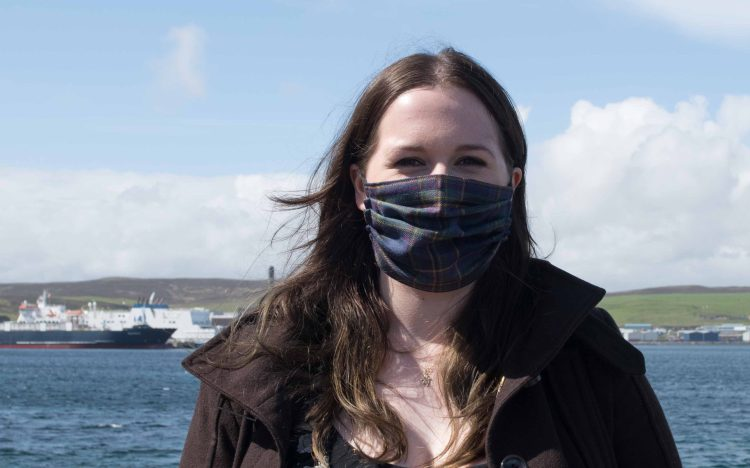 Emma, a young dark-haired woman, looks into the camera. The seafront is behind her with ships in the background. She is wearing a tartan face covering.
