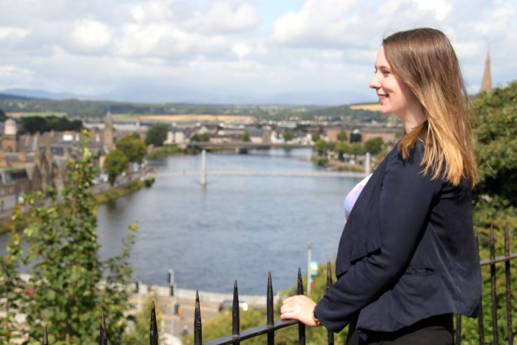 Emma, a young woman with light brown hair, stands at the railings of Inverness castle. She is smiling while looking out over the city