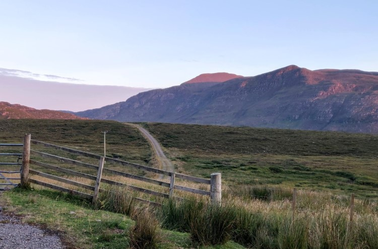 Landscape shot. The image looks down a path through fields and over the mountains at sunset