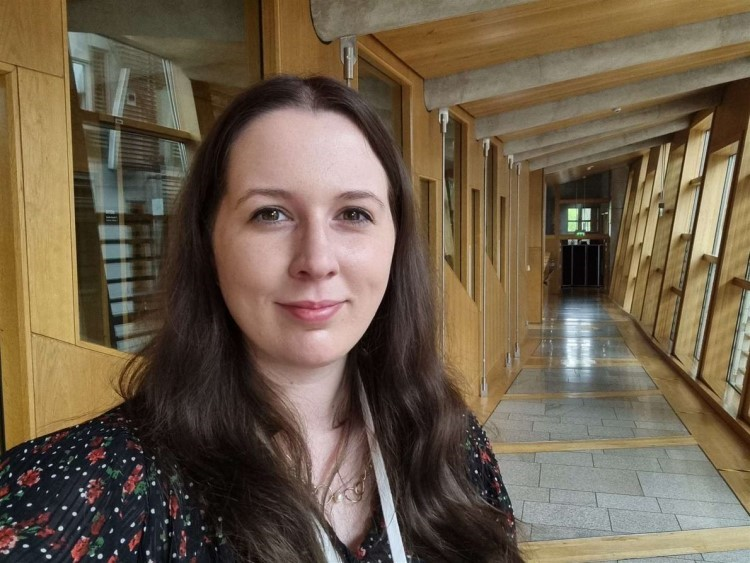 Emma stands in a Holyrood corridor smiling into the camera