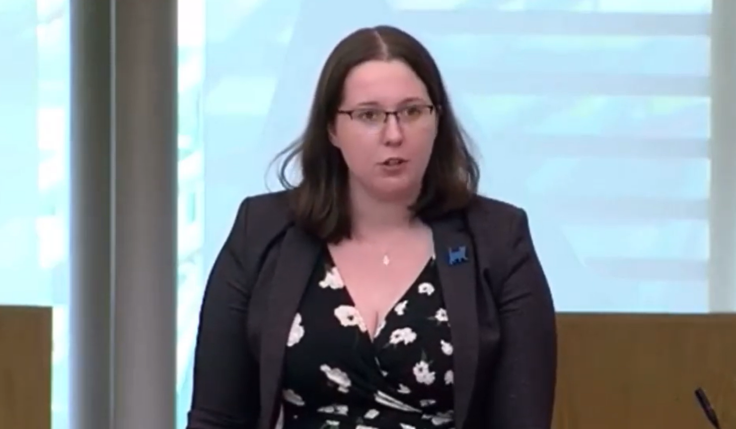 Still from a video in the Scottish Parliament debating chamber. Emma Roddick, 24yo in a black dress and grey blazer with a small blue cat pin, wearing glasses, speaks to someone off-camera.