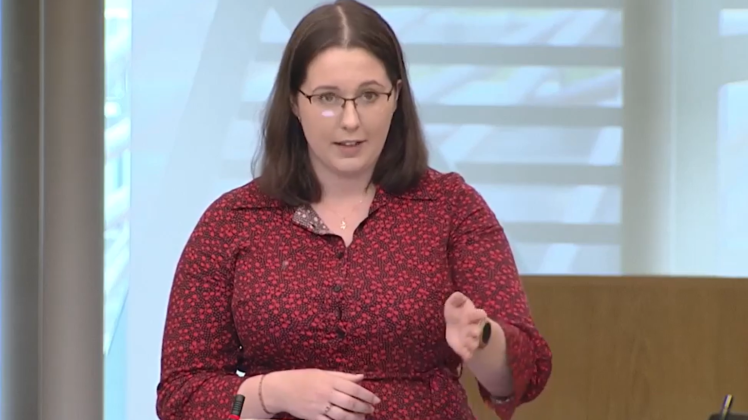 Still from a video. Emma Roddick, 24yo with shoulder-length brown hair and brown glasses and a red dress on, gestures while making a speech in the Scottish Parliament debating chamber.