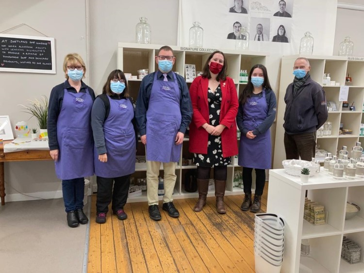 Emma stands fourth from the left with five employees of the Shetland Soap Company on their shop floor