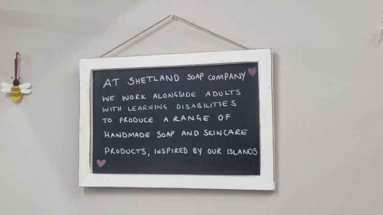 """A hand-written sign at the Shetland Soap Company which reads """"We work alongside adults with learning disabilities to produce a range of handmade soap and skincare products, inspired by our islands"""""""